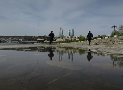 Two men run next to the Caspian Sea as the Flame Towers are reflected in a puddle in Baku, Azerbaija